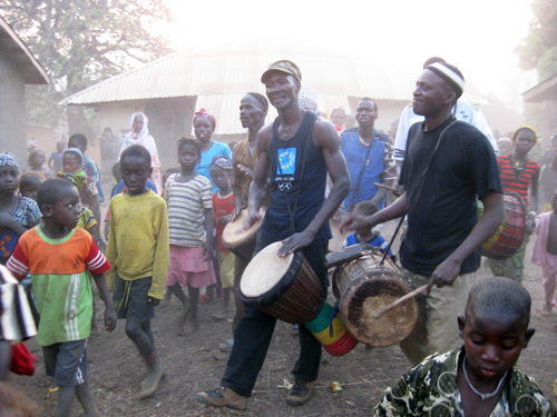 Sayon playing in his village for the children.