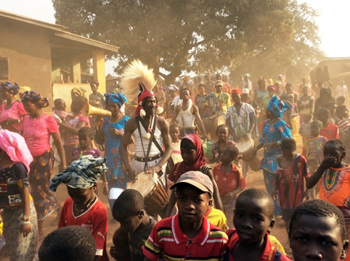 Sayon leading the drums through his village to celebrate a new well.